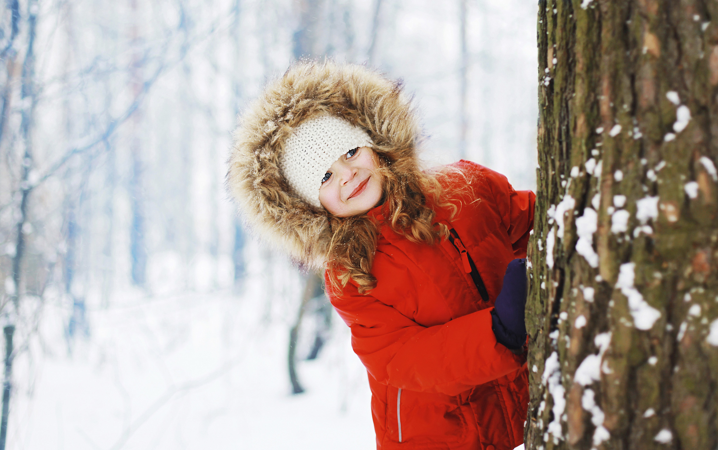 Child having fun outdoors with snowball in winter snowy forest